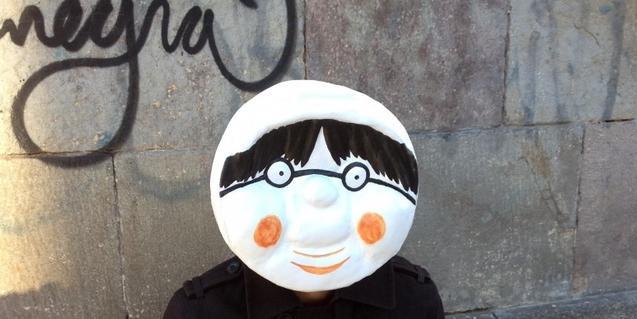 Un fotomuntatge que mostra una persona amb la cara dibuixada davant d'un mur amb una pintada