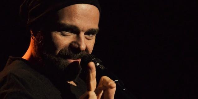 Retrat de l'artista amb una gorra al cap i amb un micro a la mà durant una actuació