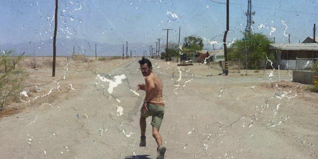 Una fotografia aparentment deteriorada que mostra un home corrent per una carretera
