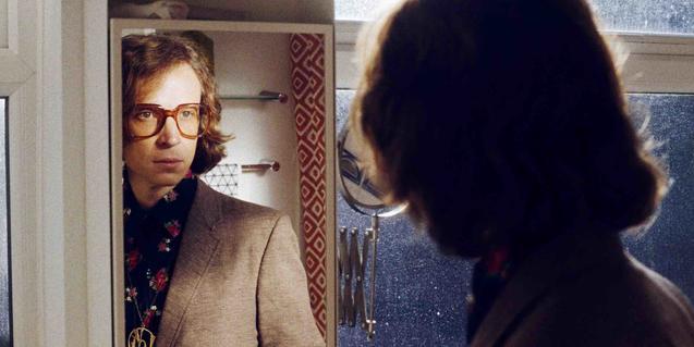 Retrat del músic amb grans ulleres de pasta mirant-se al mirall d'una cambra de bany