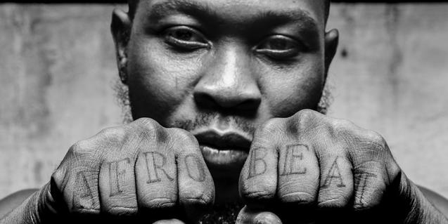 Retrato de primer plano del músico africano mostrando los tatuajes que lleva en las manos