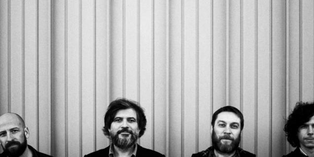 Los integrantes de la banda retratados de cabeza para arriba contra un fondo monocromático