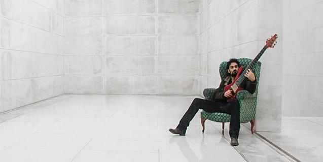 L'artista retratat en una gran sala assegut en una butaca amb el baix a les mans