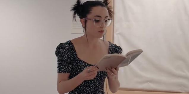 La poeta Maria Sevilla Paris amb ulleres i el cabell recollit llegint els seus versos davant d'una de les obres exposades