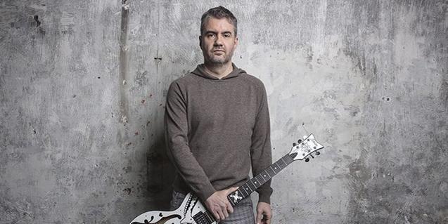 L'artista retratat amb la guitarra a la mà contra una paret