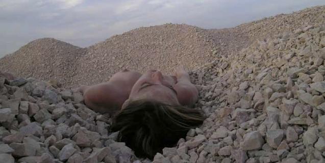 Una fotografia d'Eva Davidova que mostra una noia nua tombada sobre unes muntanyes de pedres