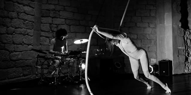 Una de les intèrprets amb la corda llisa amb un músic tocant la bateria al darrere