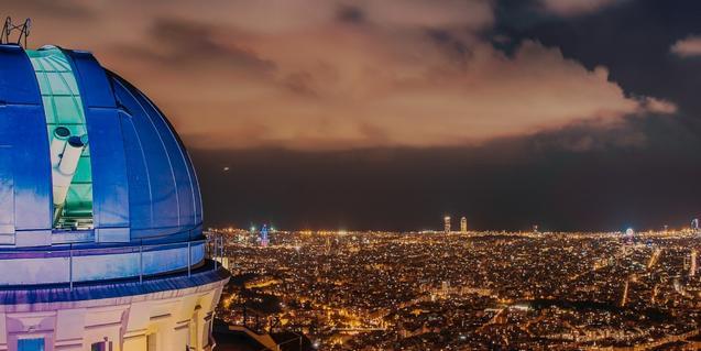 Imatge nocturna de l'Observatori Fabra amb Barcelona al fons