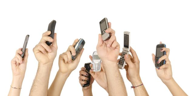 Una imagen de la exposición de Paco Chanivet que muestra unas manos levantadas y sujetando teléfonos móviles