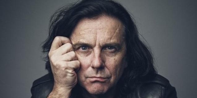 Retrat de primer pla del músic britànic tocant-se la cara amb la mà