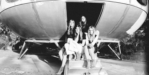Les quatre germanes Findlay retratades al peu d'una estructura amb forma de gran nau espacial