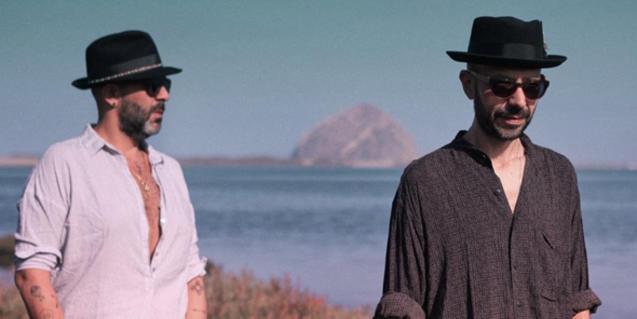 Els dos components del duet retratats amb barret davant del mar