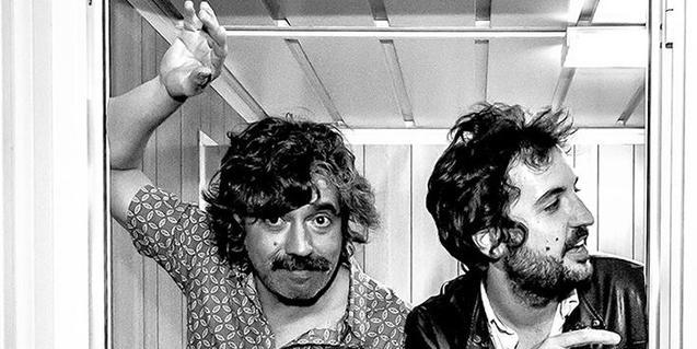 Retrato en blanco y negro de los integrantes de la banda, apoyados en el quicio de una puerta