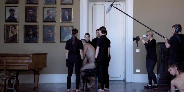 Unes noies vestides de negre envolten un home despullat en una de les performances de Joan Morey