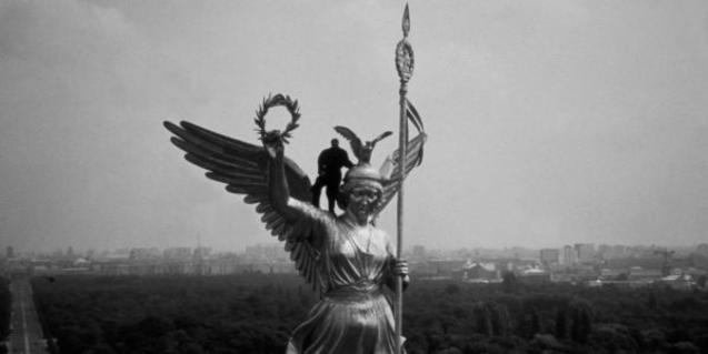 A man high up on the statute of an angel.