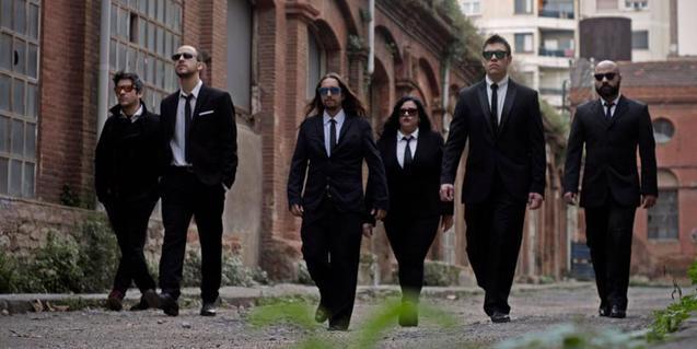 Els sis integrants d ela banda, amb vestits negres i caminant per un paisatge industrial