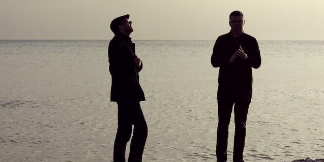 Els dos integrants del grup, fotografiats a contrallum en una platja