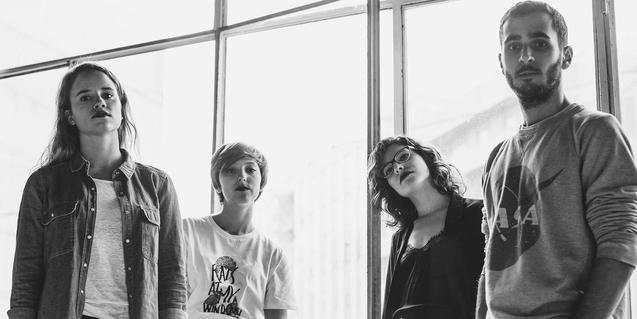 Retrato en blanco y negro de los cuatro integrantes de la banda ante una ventana