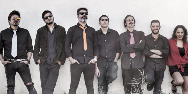 Retrato de los siete miembros de la banda apoyados contra una pared