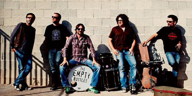 Retrato del grupo en exteriores y alrededor de una batería con el nombre de la banda