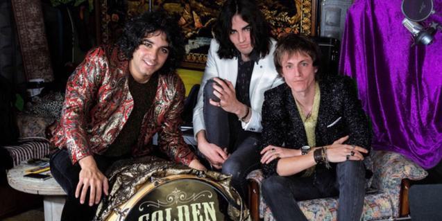 Els tres integrants de la banda retratats al voltant d'una bateria