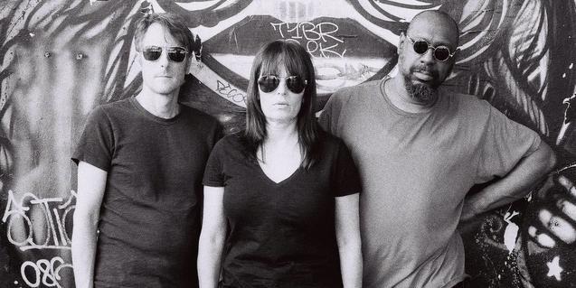 Los tres miembros de la banda con gafas de sol y ante un grafiti