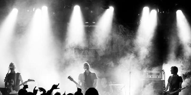 Una imagen en blanco y negro de la banda actuando sobre un escenario lleno de humo blanco