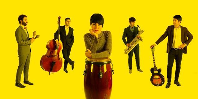 Retrato de grupo de los músicos con sus instrumentos sobre un fondo amarillo
