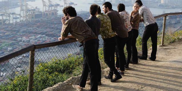 Los integrantes de la compañía de espaldas contemplando el puerto de Barcelona desde un mirador