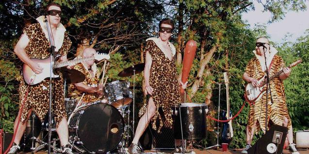 Los miembros del cuarteto vestidos con piel de leopardo y un garrote en la mano