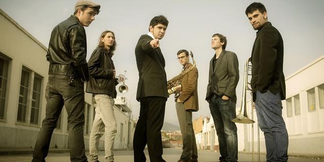 Els sis membres de la formació, retratats en exteriors amb els seus instruments musicals