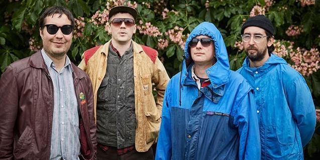 Els quatre integrants del grup retratats a l'aire lliure amb vestits de pluja