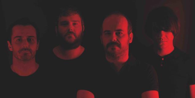 Retrato de los cuatro miembros de la banda en una penumbra de tonos rojizos