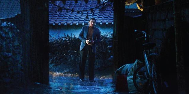 Un fotograma del film con uno de los protagonistas a punto de cruzar una puerta de un edificio tradicional