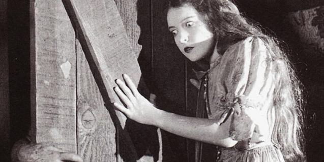 Un fotograma del film en blanc i negre on es veu una noia atemorida tancant una porta