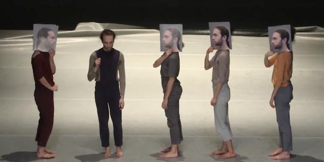 Un moment de la coreografia amb els intèrprets en filera i portant unes fotografies de rostres que els tapen la seva cara autèntica
