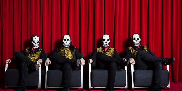 Els quatre membres de la banda amb màscares de calaveres i asseguts en un sofà