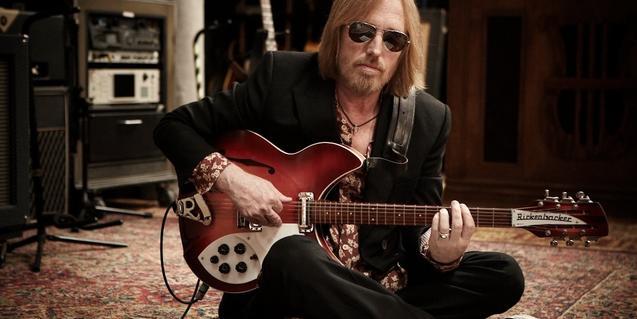 Retrato del músico con gafas de sol sentado en el suelo y tocando una guitarra
