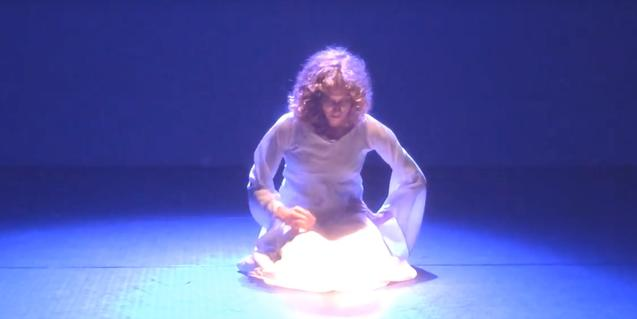 Una de las intérpretes vestida de blanco y bañada en luz en el centro de la escena en un momento del montaje