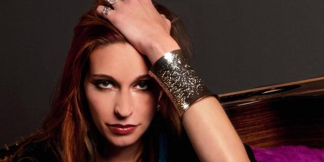 Retrato de la cantante norteamericana con la mano en la cabeza y una gran pulsera en la muñeca