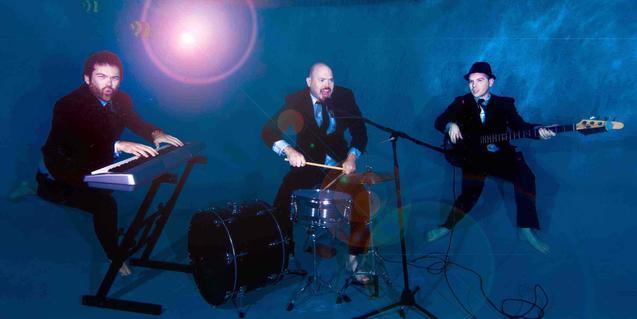 Els tres membres de la banda descalços i en plena actuació