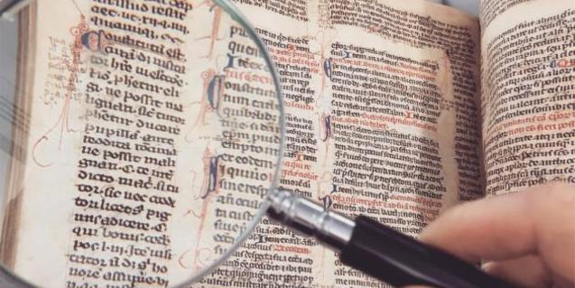 Fotografía de un manuscrito antiguo y una lupa