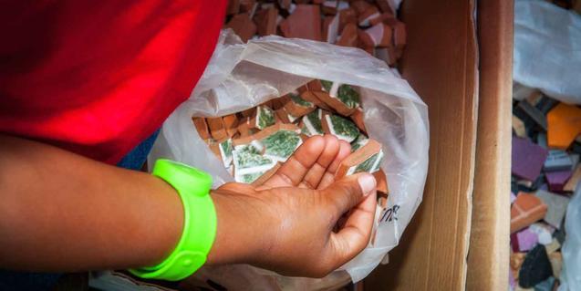 Fotografía de unas manos de niño manipulando trozos de cerámica