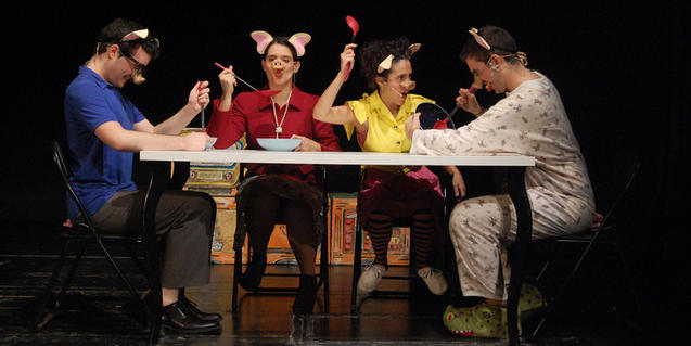 Fotografía del espectáculo, cuatro actores haciendo de cerditos en una mesa comiendo