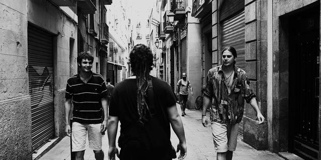 Els tres integrants de la formació retratats en blanc i negre en un carrer de Ciutat Vella amb dos músics de cara i un d'esquenes