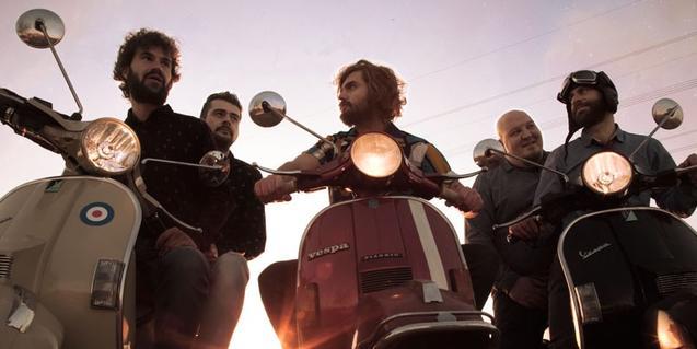 Els cinc membres de la formació retratats mentre munten en moto