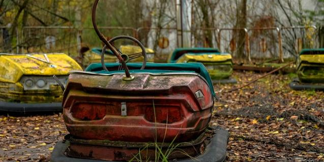 Un parque de atracciones abandonado con los autos de choque enmohecidos en primer plano