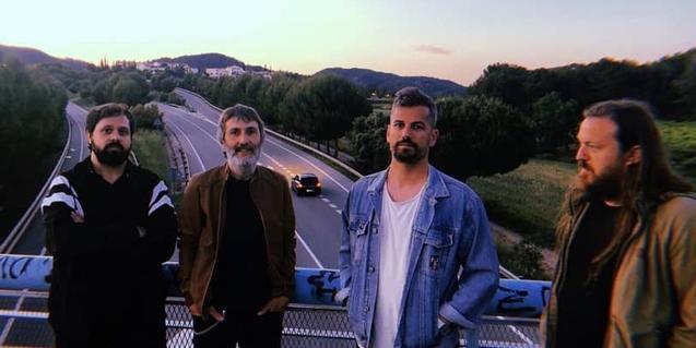 Los cuatro integrantes de la formación retratados sobre el puente de una autopista