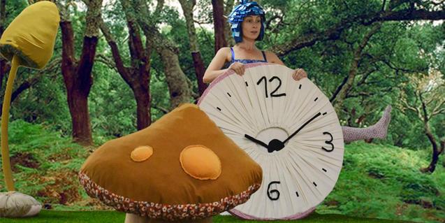 Escena del espectáculo, actriz con un reloj gigante.