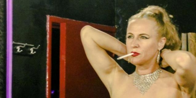 L'actriu de cabaret amb un cigarret als llavis i posant-se un collaret